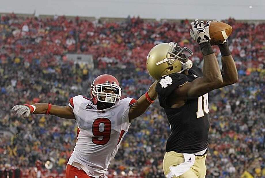 Notre Dame  wide receiver Duval Kamara (18) makes a 12-yard touchdown reception while being defended by Utah  cornerback Conroy Black (9) during the third quarter of an NCAA college football game in South Bend, Ind., Saturday, Nov. 13, 2010. Photo: Darron Cummings, AP