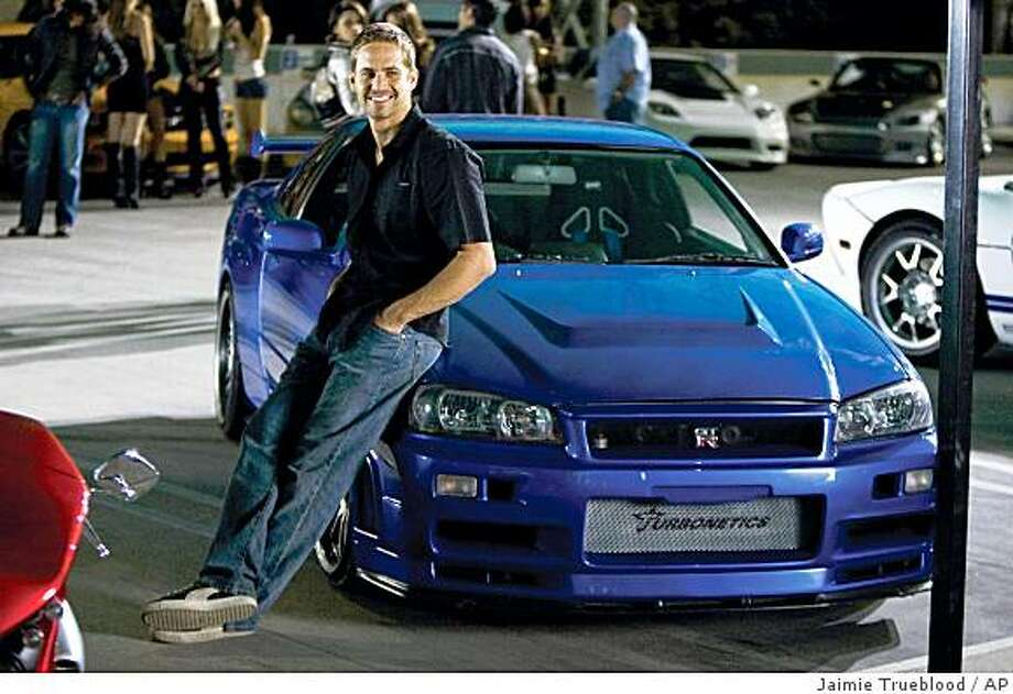 "In this film publicity still released by Universal Pictures, Paul Walker, as agent Brian O'Conner, leans against his 1998 Nissan Skyline GTR in a scene from ""Fast & Furious."" Photo: Jaimie Trueblood, AP"