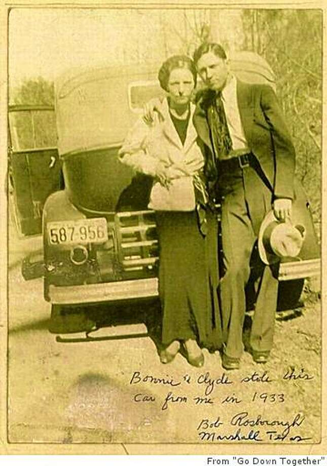 """Bonnie and Clyde in spring 1933. This photo was taken from unprocessed film discovered by police following an April 13 gun battle in Joplin, Missouri. The Barrow gang had yet to learn that exposed car license plates like the one in this picture made it easier for their pursuers to track them. / From """"Go Down Together"""" Photo: From """"Go Down Together"""""""