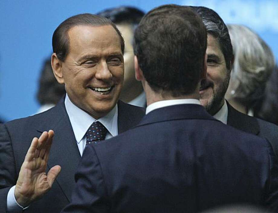 Russian President Dmitry Medvedev, front, listens to Italy's Prime Minister Silvio Berlusconi, left, during the official family photo at the G20 Summit in Seoul, South Korea, Friday, Nov. 12, 2010. Photo: Dmitry Astakhov, Associatd Press