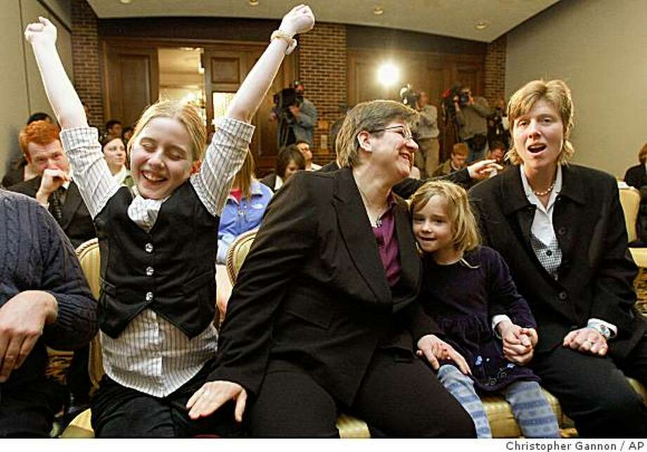Dawn BarbouRoske, second from left, of Iowa City, leans towards her partner, Jen BarbouRoske after learning of the Iowa Supreme Court ruling in favor of legalizing gay marriage in Des Moines, Iowa on Friday, April 3, 2009. Between them is their daughter Bre, 6. Their other daughter, McKinley, 11, reacts to the ruling at left. (AP Photo/The Des Moines Register, Christopher Gannon) Photo: Christopher Gannon, AP