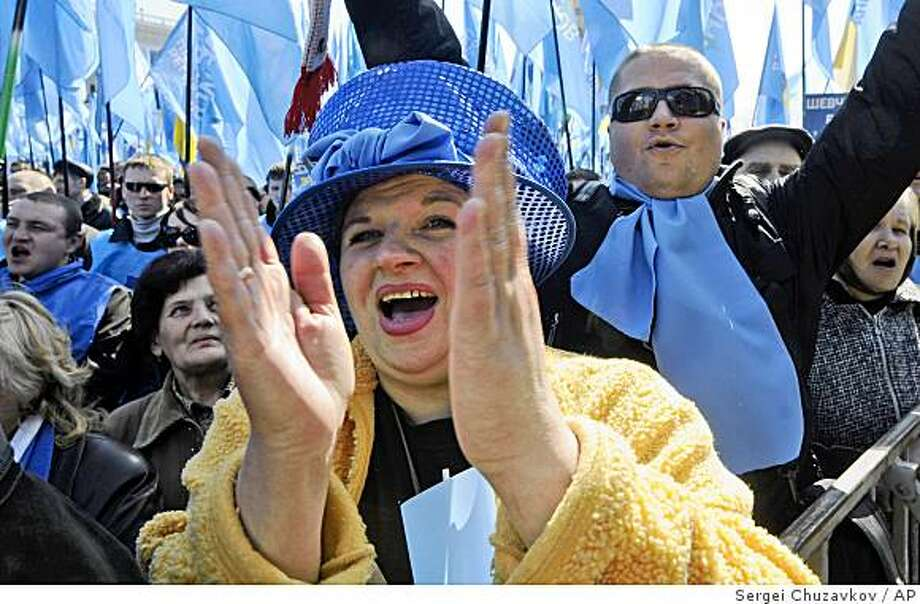 """Supporters of the Party of Regions, shout during a rally  in Kiev, Ukraine, Friday, April 3, 2009. Thousands of Ukrainians are protesting government polices amid a worsening financial crisis and demanding early parliamentary elections. More than 15,000  protesters waved the Party of Regions blue flags and chanted """"No!"""" on Kiev's main square Friday. This was the latest round of opposition rallies in this ex-Soviet republic struggling to avoid an economic collapse. (AP Photo/Sergei Chuzavkov) Photo: Sergei Chuzavkov, AP"""