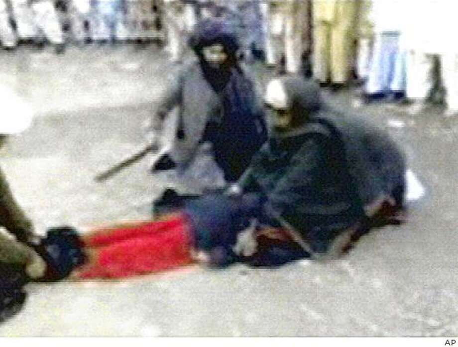 In this undated image taken from mobile phone footage released by Dunya TV Channel shows a woman in a body-covering burqa face down on the ground with two men holding her arms and feet and a third man whipping her backside, on Friday, April 3, 2009. Pakistani authorities ordered an investigation Friday into a video showing a man flogging a screaming woman in the country's northwest where the government recently agreed to introduce Islamic law to end a rebellion by Taliban militants. (AP Photo/Dunya TV Channel) ** NO SALES NO ARCHIVE - THE ASSOCIATED PRESS IS UNABLE TO INDEPENDENTLY VERIFY THE AUTHENTICITY, CONTENT, LOCATION OR DATE OF THIS HANDOUT IMAGE FROM VIDEO RELEASED BY DUNYA TV** Photo: AP