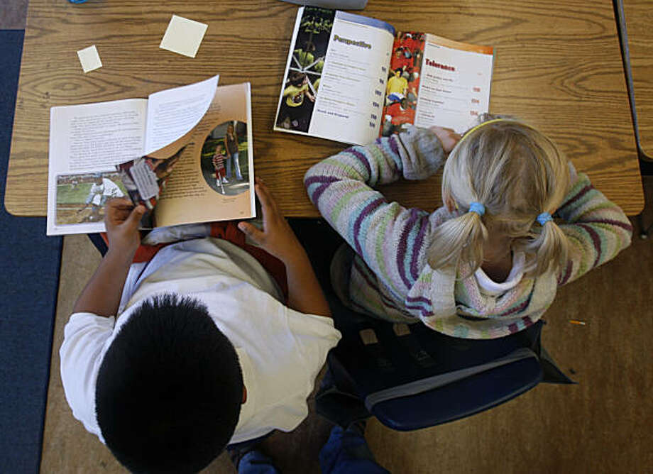 Fourth-graders Ricardo Arrona (left) and Sera Benjamin read textbooks in Missy Read's literacy class at John Muir Elementary School in San Francisco, Calif., on Friday, Nov. 12, 2010. Read is the full-time literacy coach at the school. Photo: Paul Chinn, The Chronicle