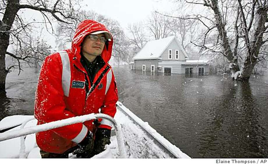 ** CORRECTS TO MOORHEAD, MINN **U.S. Geological Survey hydrologist Joel Galloway pilots a small boat past flooded homes Monday, March 30, 2009, in Moorhead, Minn. Weary residents welcomed the Red River's further retreat Monday but faced an approaching snowstorm expected to kick up wind-whipped waves that could threaten the sandbag levees they built to protect their city from a major flood.  (AP Photo/Elaine Thompson) Photo: Elaine Thompson, AP