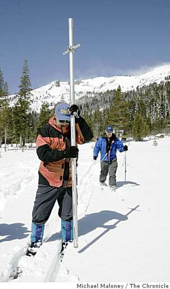 Frank Gehrke of the state Department of Water Resources' Snow Survey (left) drives a hollow tube into the snow to measure snow depth and to take a sample. At right is Dave Hart also of the state Department of Water Resources' Snow Survey. At the Phillips Survey Station near Echo Summit, state officials today took their penultimate Sierra snow survey for the season, and the news was grim. Photo: Michael Maloney, The Chronicle