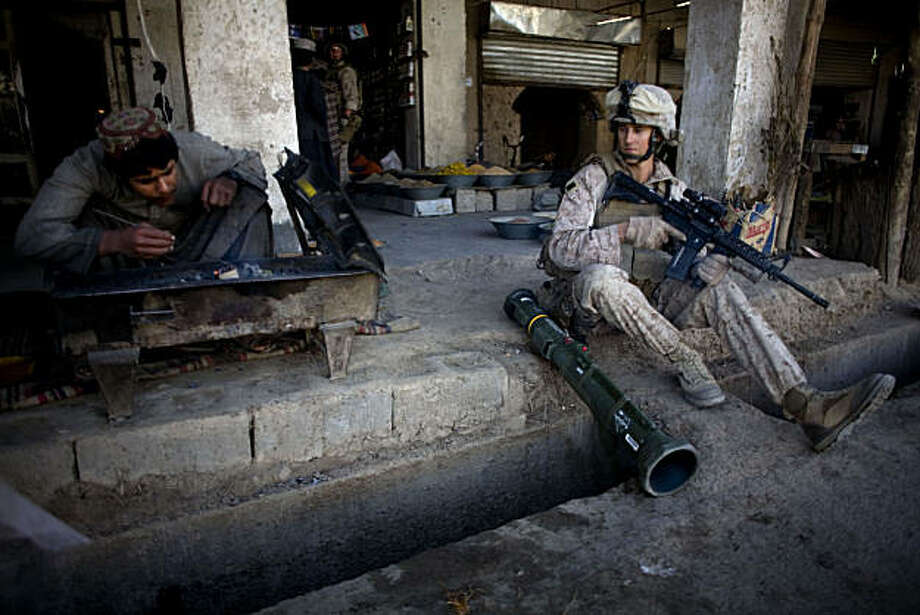 Lance Cpl. Brian Flower, of Chico, Calif., with India Company, 3rd Battalion 5th Marines, First Marine Division, sits at a bazaar during a patrol, Friday, Nov. 12, 2010 in Sangin, Afghanistan. Photo: Dusan Vranic, AP