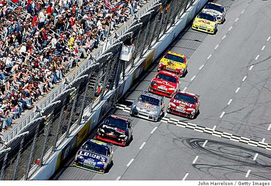 MARTINSVILLE, VA - MARCH 29: Jimmie Johnson, driver of the #48 Lowe's Chevrolet, leads Denny Hamlin, driver of the #11 FedEx Express Toyota, and a pack of cars during the NASCAR Sprint Cup Series Goody's Fast Pain Relief 500 at the Martinsville Speedway on March 29, 2009 in Martinsville, Virginia.  (Photo by John Harrelson/Getty Images) Photo: John Harrelson, Getty Images