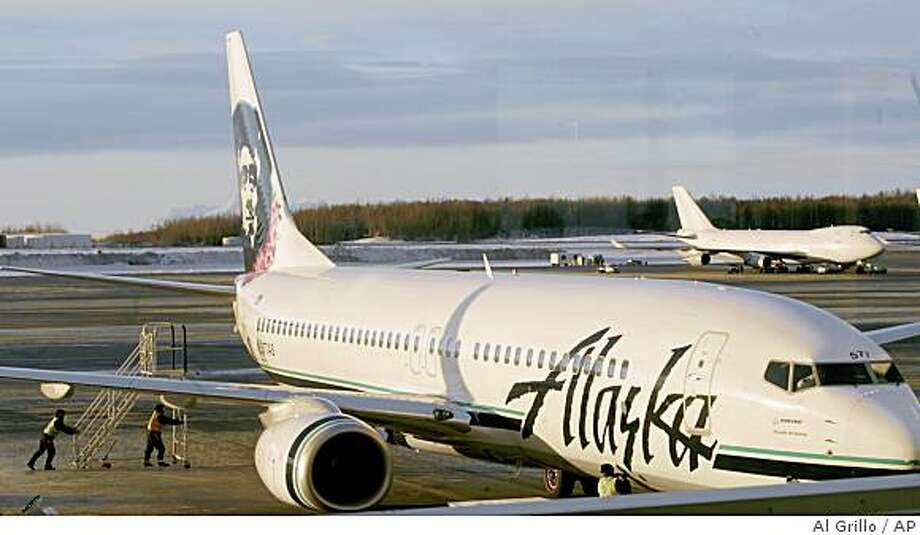 **FOR IMMEDIATE RELEASE ** An Alaska Airlines jet with a Hawaiian Lei around their signature Eskimo on the tail, pulls into the gate at the Ted Stevens International Airport in Anchorage, Alaska Sunday, Dec. 16, 2007, to board passengers for Hawaii. The Seattle-based Alaska Airlines recently acquired rival carrier Hawaiian Vacations Inc. and is now the only airline to fly from Alaska to Hawaii. (AP Photo/Al Grillo) Photo: Al Grillo, AP
