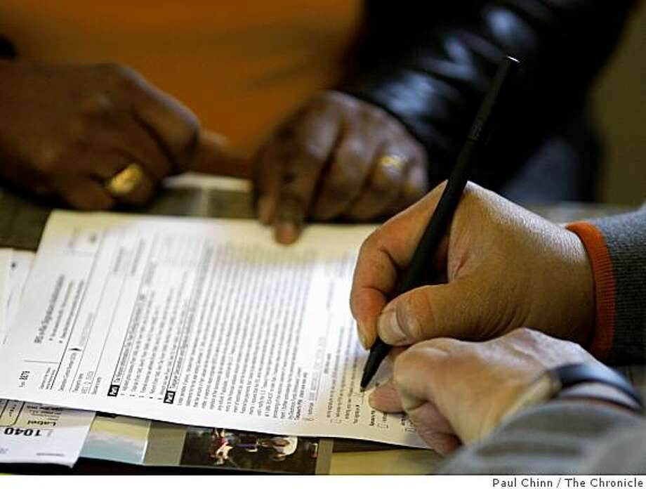 A client signs his income tax return after it was prepared free of charge at the San Antonio Community Development Corporation in Oakland, Calif., on Wednesday, March 25, 2009. Photo: Paul Chinn, The Chronicle