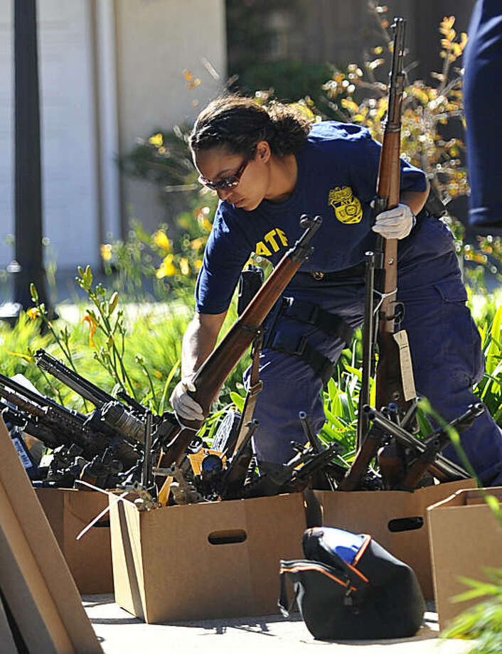An Alcohol Tobacco and Firearms officer confiscates guns during a raid on a home Tuesday, Nov. 2, 2010, in San Clemente, Calif.  A suspect was arrested at the house on alleged weapons trafficking charges. Photo: Richard Hartog, AP