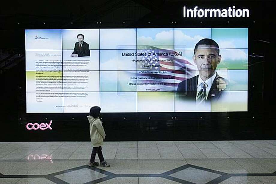 At the entrance of the summit venue, a child watches President Barack Obama during a slide show featuring the visiting leaders to the upcoming G-20 Summit, Tuesday, Nov. 9, 2010, in Seoul, South Korea. Twenty world leaders will come together in Seoul fromNov. 11-12 to discuss the state of the global economy as it emerges from the financial crisis. Photo: Wally Santana, AP