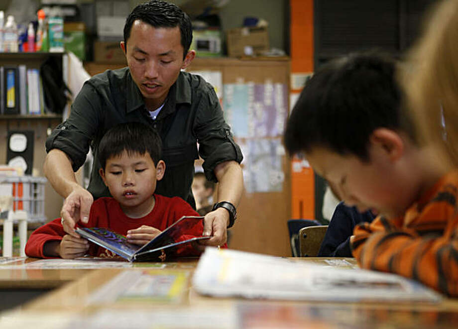 Special Day Class teacher, Daryl Tran reads to Grattan Elementary student Kevin Lao, 8, during class on Tuesday April 13 2010 in San Francisco, Calif. The equipment is designed to help students with autism have and easier time playing with other students. The school has at least 28 students with autism and tries to incorporate their presence into a normal part of daily life on campus. Photo: Mike Kepka, The Chronicle
