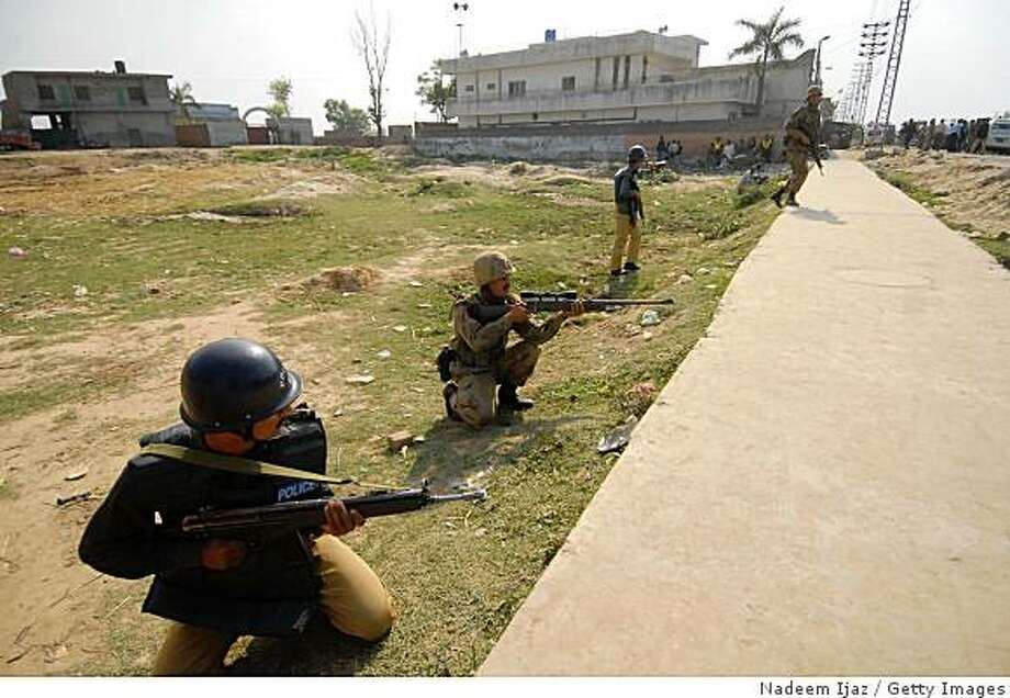 LAHORE, PAKISTAN - MARCH 30:  Pakistan police officers take cover during a siege at the Manawan police training school on March 30, 2009 in Lahore, Pakistan. The armed group stormed the academy just outside of the city leaving 18 dead according to Pakistan's Interior Ministry, with nearly 100 injured. The storming follows the recent attack on the Sri Lankan cricket team also in Lahore less than a month ago.  (Photo by Nadeem Ijaz/Getty Images) Photo: Nadeem Ijaz, Getty Images