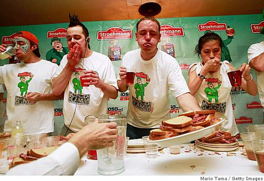 NEW YORK - MARCH 16:  Competitive eaters (L to R) Tim Janus, Pat Bertoletti, Joey Chestnut and Juliet Lee face off in the first-ever Stroehmann Sandwich Slamm, an eating contest featuring corned beef and rye sandwiches ahead of St. Patrick's Day, March 16, 2009 in New York City. Winner Pat Bertoletti consumed 16 3/4 sandwiches in ten minutes to win the contest at Gallagher's Steakhouse.   (Photo by Mario Tama/Getty Images) Photo: Mario Tama, Getty Images