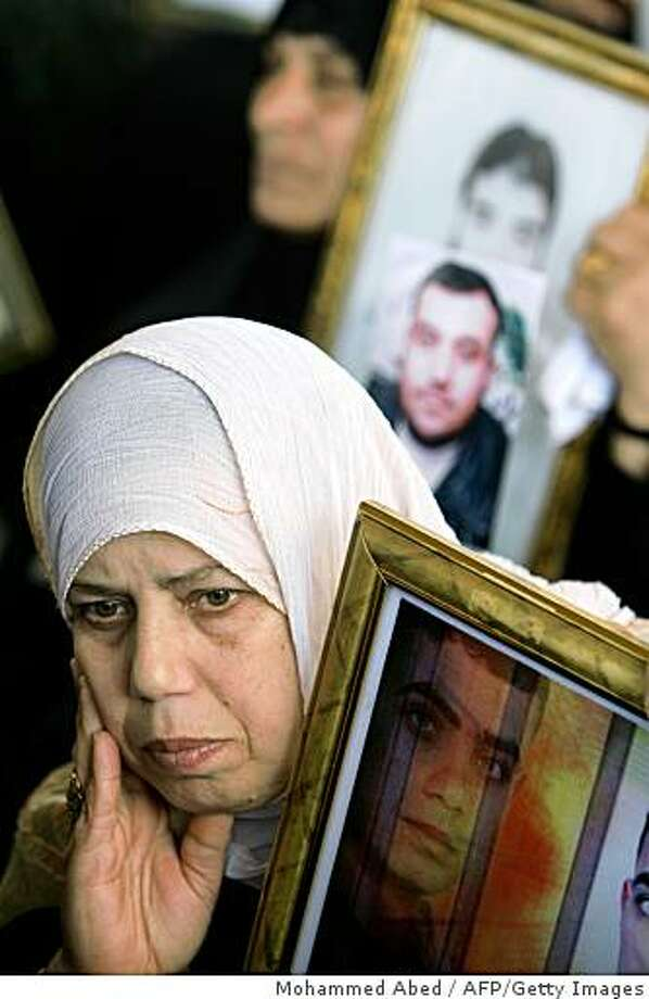 Palestinian women hold portraits of jailed relatives during a protest at the Red Cross offices in Gaza City to demand the release of Palestinian prisoners held in Israeli jails on March 30, 2009. More than 11000 Palestinians are currently held in Israeli prisons. AFP PHOTO/MOHAMMED ABED (Photo credit should read MOHAMMED ABED/AFP/Getty Images) Photo: Mohammed Abed, AFP/Getty Images