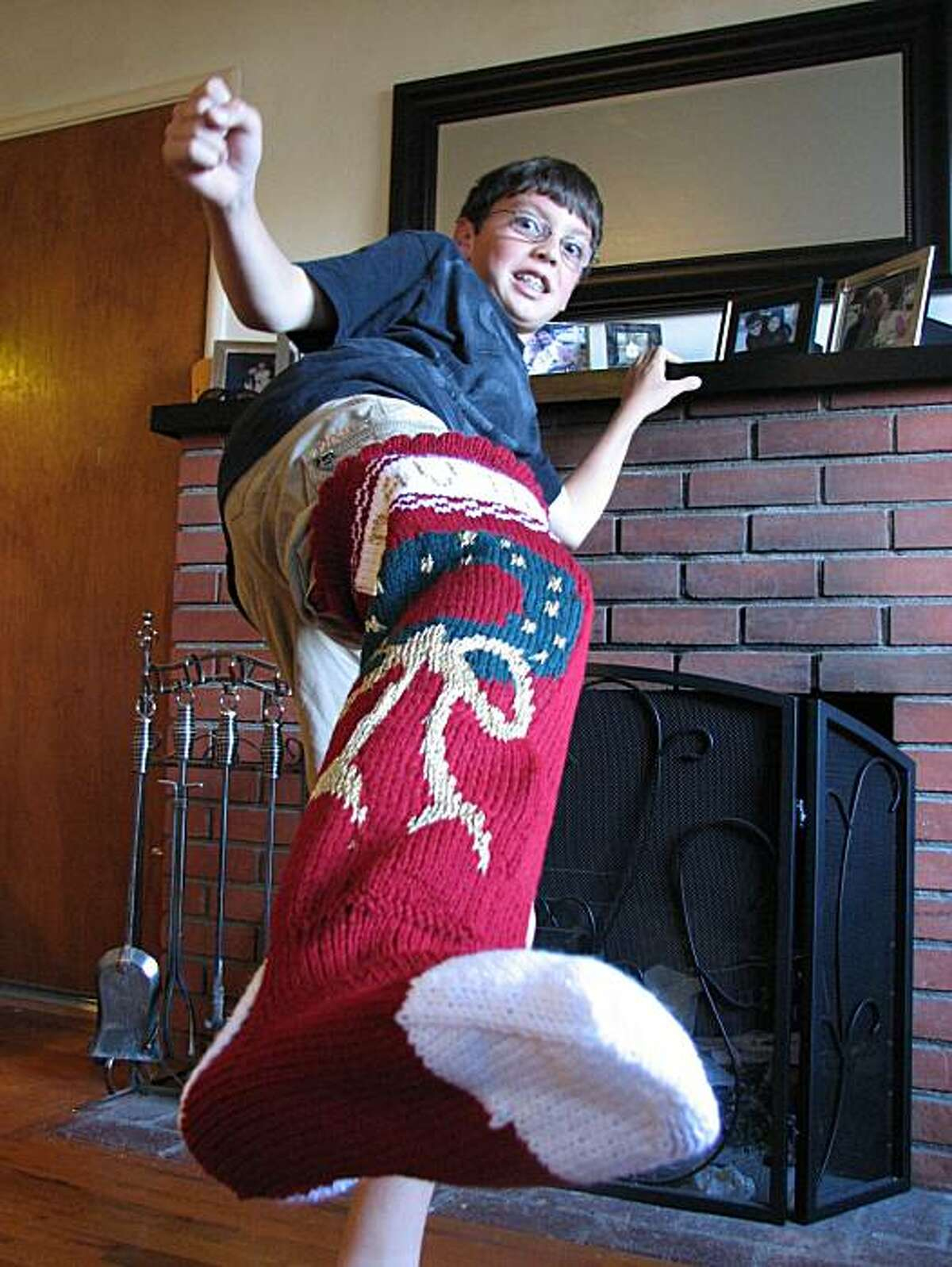 David Twohig, 12, of Pacific Grove, CA, tests the space capacity of a Grandma May Christmas stocking.