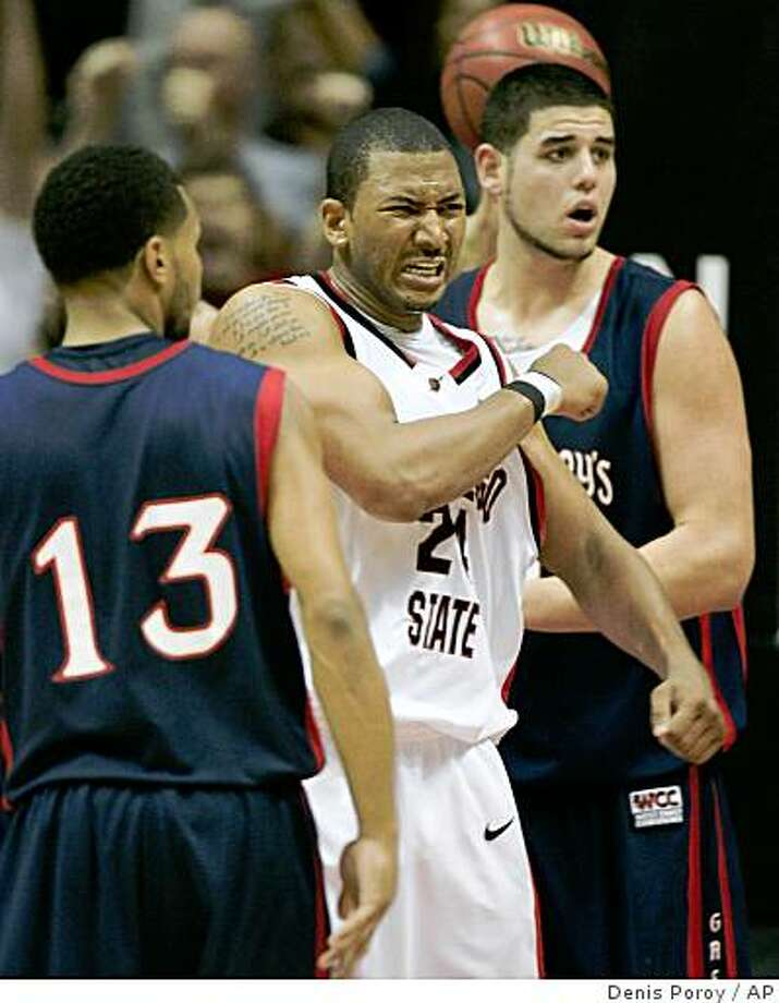 San Diego State's Tim Shelton, center, celebrates after scoring between St. Mary's Patrick Mills, left, and Omar Samhan, right, during the second half of a quarterfinal NIT college basketball game Wednesday, March 25, 2009 in San Diego.  San Diego State won 70-66. (AP Photo/Denis Poroy) Photo: Denis Poroy, AP