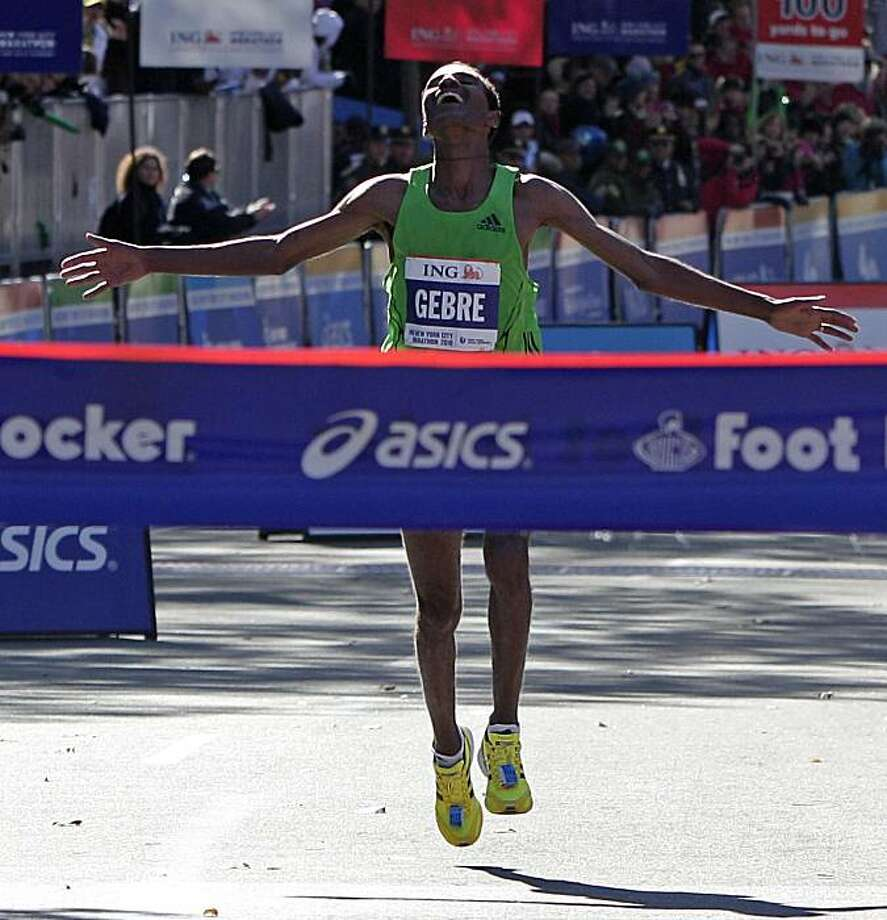 Gebre Gebrmariam, of Ethiopa, throws out his arms before breaking the tape to win the professional men's division at the New York City Marathon in New York, Sunday, Nov. 7, 2010. Photo: Kathy Willens, AP