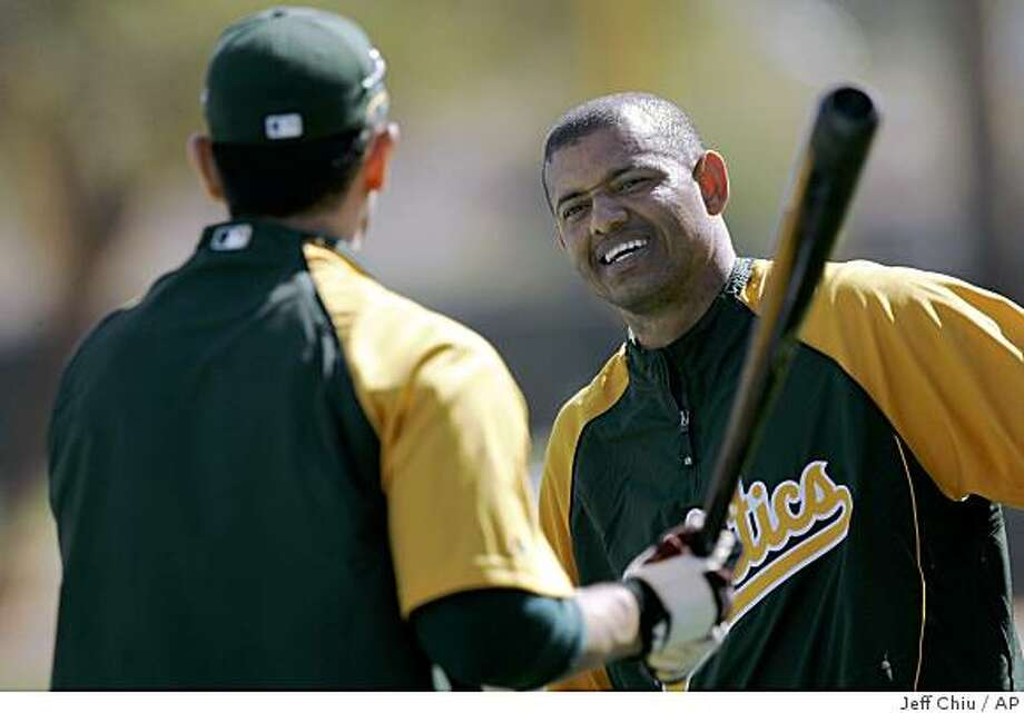 Oakland Athletics' Orlando Cabrera, right, laughs with teammate Nomar Garciaparra before they played the Arizona Diamondbacks in a spring training baseball game in Phoenix, Thursday, March 12, 2009. Neither Cabrera nor Garciaparra played in the game. (AP Photo/Jeff Chiu) Photo: Jeff Chiu, AP