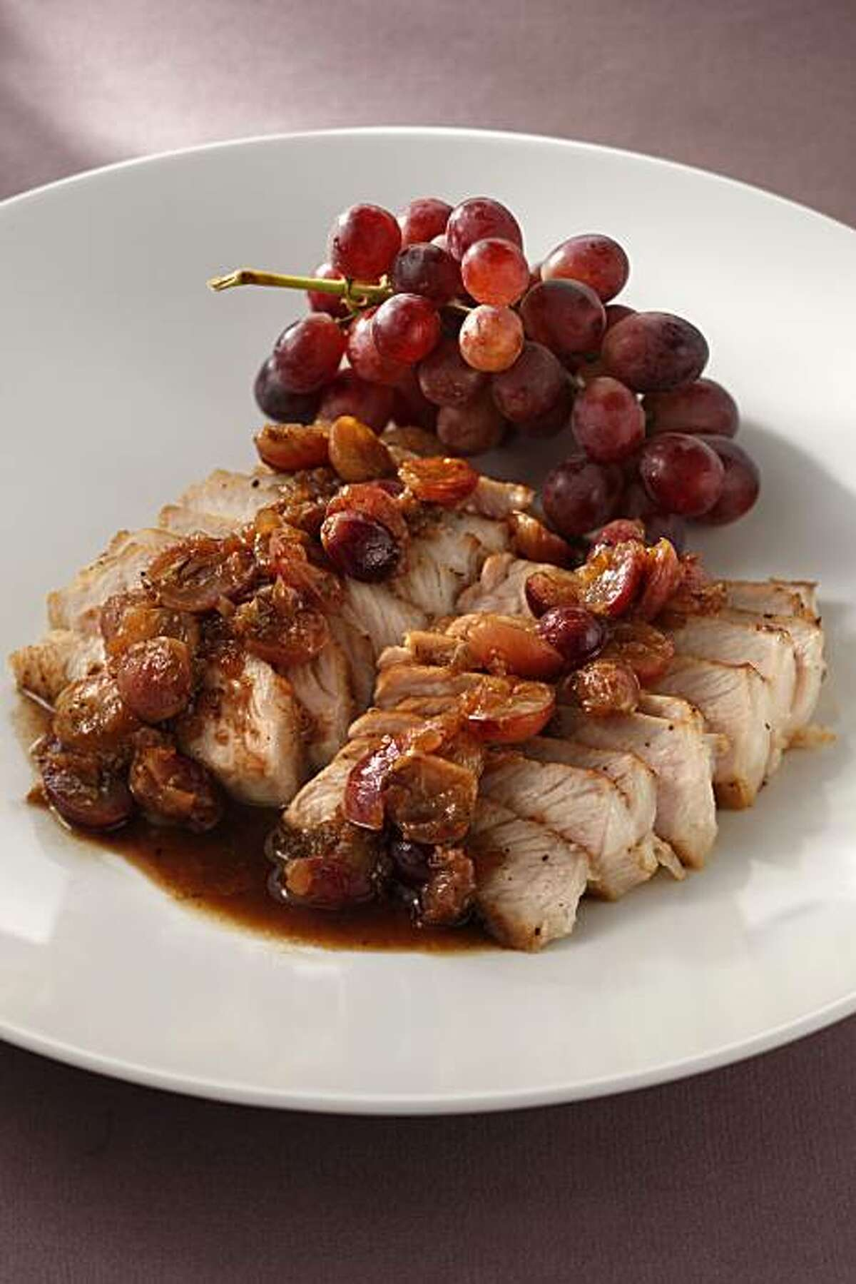 Pork with grapes and onions is seen in San Francisco, Calif., on October 13, 2010. Food styled by Lynne Char Bennett.