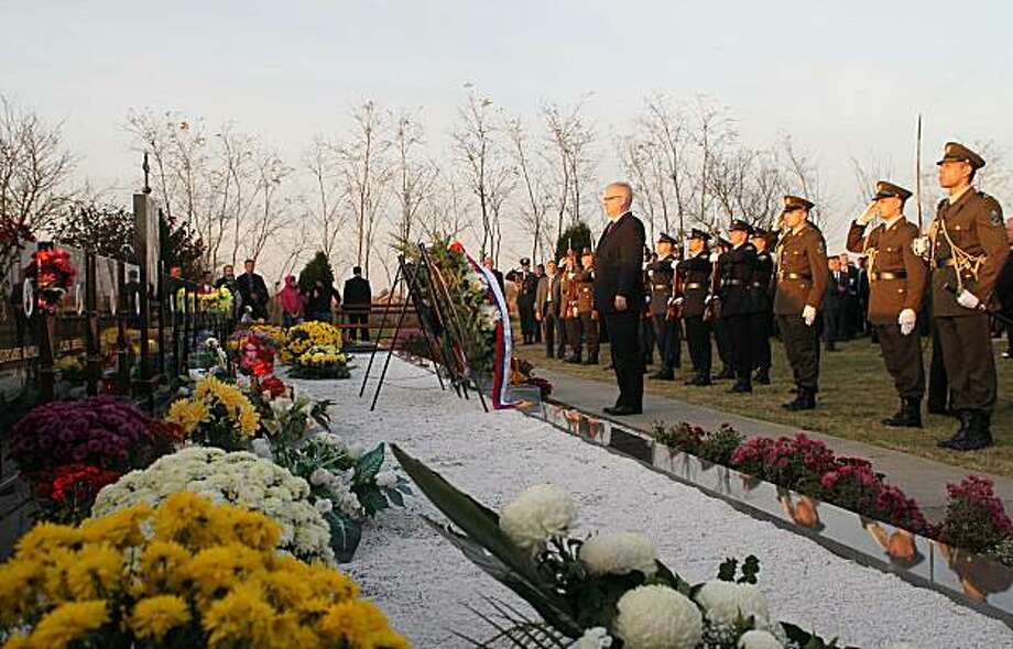 Croatian President Ivo Josipovic, center, paying respect for 18 Serbs killed by Croats in a village of Paulin Dvor, eastern Croatia, Thursday, Nov. 4, 2010. Serbian President Boris Tadic apologized Thursday at the site where more than 200 Croats were massacred, offering the strongest condemnation to date by a leader from Serbia of wartime atrocities committed by the country. Photo: Darko Vojinovic, AP