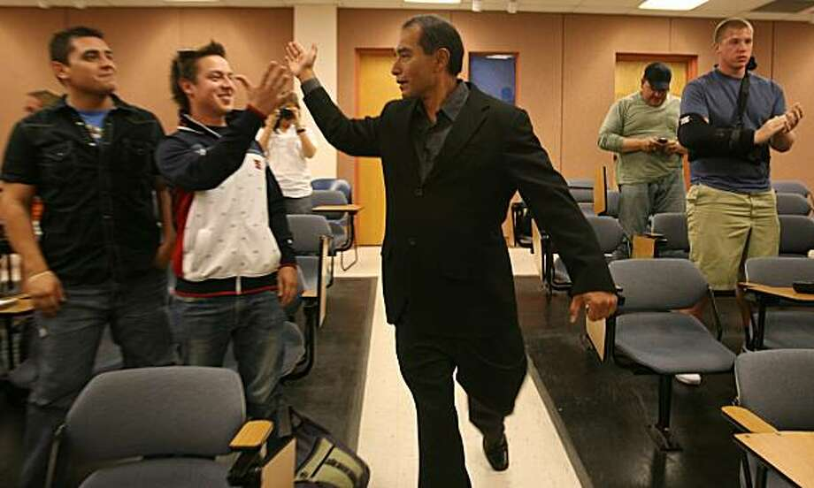 In this photo from Oct. 20, 2010, Bravo Cadillac and Chevrolet owner Raymond Palacio greeted University of Texas at El Paso students Manuel Acosta, left, and Eder Diaz, second from left, as he entered a Business Administration room for a talk with students, in El Paso, Texas. Acosta, 25, and Diaz, 23, were shot and killed Tuesday in Ju‡rez, Mexico, Mexican and American authorities said Wednesday, Nov. 3, 2010. (AP Photo/The El Paso Times, Victor Calzada)  EL DIARIO OUT; JUAREZ MEXICO OUT; IF USE ON LAM OR LAT AND EL DIARIO DE EL PASO OUT Photo: Victor Calzada, AP