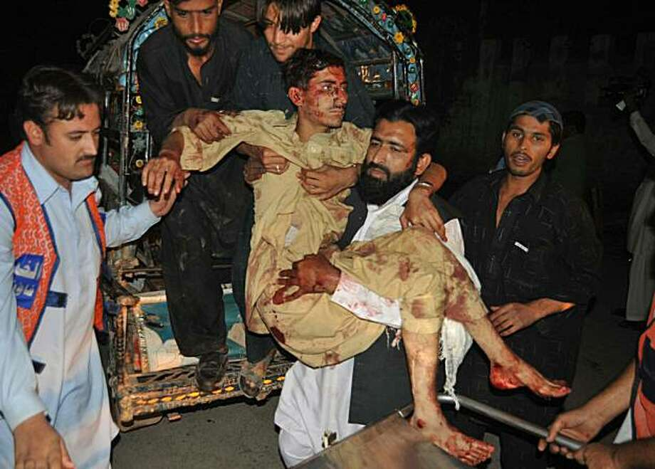 Pakistani men shift a wounded man at a hospital in Peshawar on November 5, 2010, following a grenade attack on a mosque. At least three people were killed and 14 others were wounded in a second attack on a mosque in northwestern Pakistan on November 5, ahospital official said. Photo: Hasham Ahmed, AFP/Getty Images