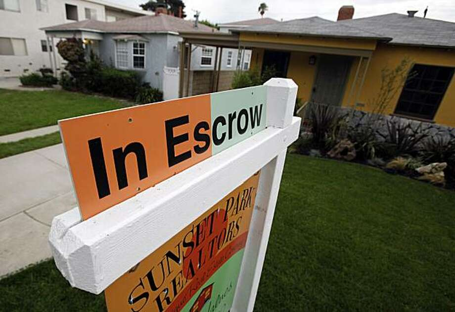 """In this Oct. 19, 2010 photo, an """"In Escrow"""" sign is added to a real estate agent's sign on a home for sale in Santa Monica, Calif. The number of people who signed contracts to buy homes fell in September after two months of gains. Photo: Reed Saxon, AP"""