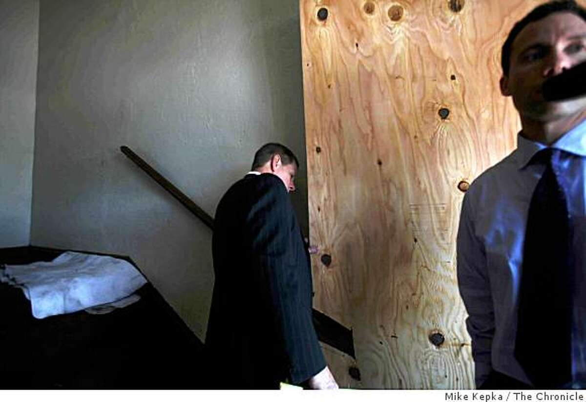 On Monday March 23, 2009 in Oakland, Calif., Attorney Michael Rains, who represents the officers involved in Saturday's shootings, investigates the entrance to the apartment involved in the shootings that left an Oakland man and 4 Oakland Police officers dead.