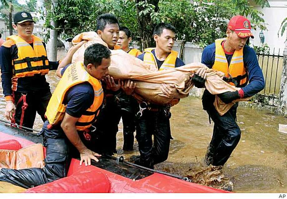 Rescuers carry the body of a victim who was killed in flash flood following dam burst in Jakarta, Indonesia, Friday, March 27, 2009. A dam burst in the outskirts of Indonesia's capital before dawn Friday, sending a flash flood into a crowded residential neighborhood, submerging hundreds of houses and killing at least 50 people, officials said. (AP Photo) Photo: AP