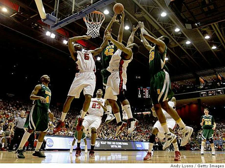 DAYTON, OH - MARCH 22: Earl Clark #5 and Preston Knowles #2 of the Louisville Cardinals go up for a rebound against Alex Franklin #42 and Edwin Ubiles #23 of the Siena Saints during the second round of the NCAA Division I Men's Basketball Tournament at the University of Dayton Arena on March 22, 2009 in Dayton, Ohio.  (Photo by Andy Lyons/Getty Images) Photo: Andy Lyons, Getty Images