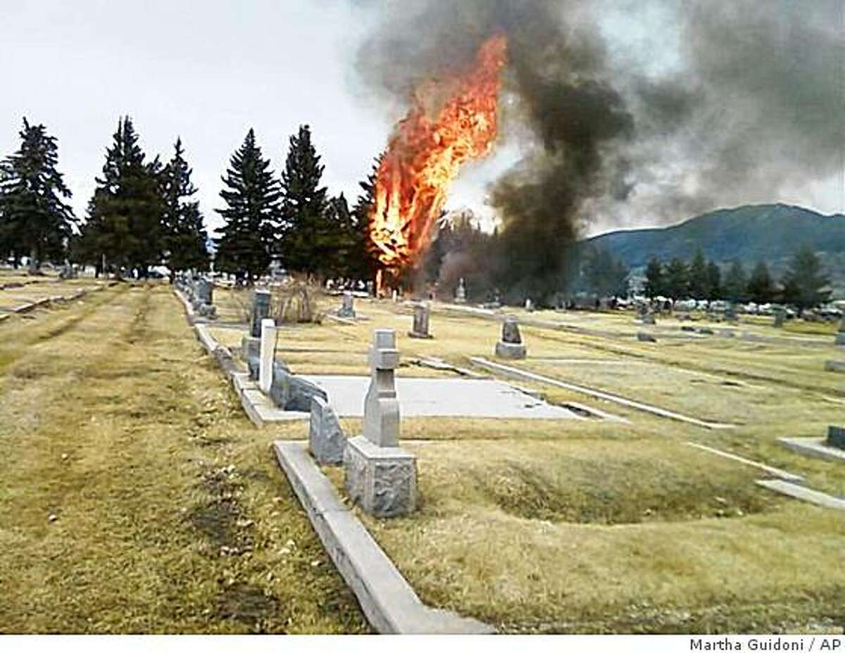 In this picture provided by Martha Guidoni via The Montana Standard, a fire burns inside the Holy Cross Cemetery after a small, singe-engine plane crashed in an area just south of the Bert Mooney Airport in Butte, Mont. on Sunday, March 22, 2009. Seventeen people, including several children, were killed in the incident, according to the Federal Aviation Administration. (AP Photo/The Montana Standard, Martha Guidoni) ** NO SALES; MANDATORY CREDIT **