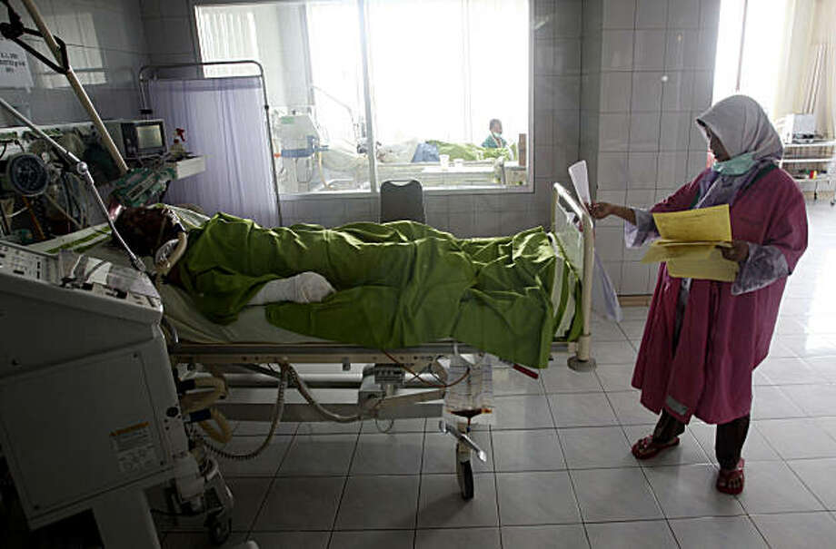 An Indonesian medic check an injured Maunt Merapi victim at hospital in Yogyakarta, Indonesia , Saturday, Nov. 6, 2010. The hospital at the foot of Indonesia's most volatile volcano is struggling to cope with victims brought in after the mountain's most powerful eruption in a century. Some have clothes, blankets and even mattresses fused to their skin. Photo: Achmad Ibrahim, AP