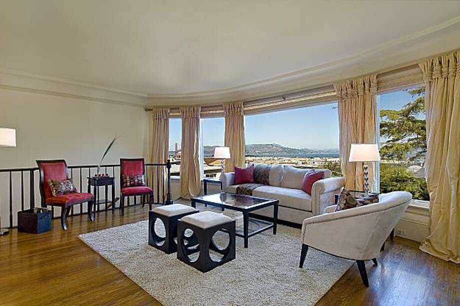 The combined living room/dining room has a gas fireplace and a wall of windows that features views of the Golden Gate Bridge. Photo: OpenHomesPhotography.com