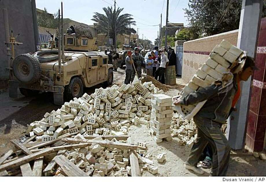 A man carries brick as his family builds additional floor at their home as a US patrol goes by in Hurriyah neighborhood  in Baghdad, Iraq, Wednesday, March 18, 2009. Eighteen months after Baghdad's sectarian blood letting eased, this city remains largely Shiite and ethnically split. Only an estimated 16 percent of the mainly Sunni Iraqi families forced from their homes in 2006 and 2007 have dared to return.(AP Photo/Dusan Vranic) Photo: Dusan Vranic, AP