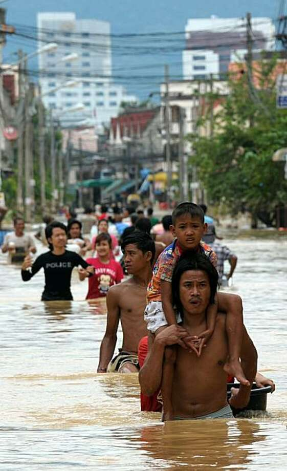 Thai villagers wade through floodwater during floods in the southern Thai city of Hat Yai on November 3, 2010.  Thai troops scrambled to reach thousands of people stranded after flash floods swept through a major southern city, as the government expressedoptimism it could reach all those trapped. Photo: Pornchai Kittiwongsakul, AFP/Getty Images