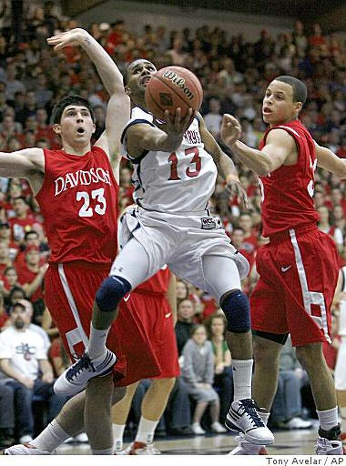 St. Mary's guard Patrick Mills, center, takes a shot over Davidson forward Steve Rossiter, left, and Stephen Curry, right, in the first half of an NIT college basketball game in Moraga, Calif., Monday, March 23, 2009. (AP Photo/Tony Avelar) Photo: Tony Avelar, AP
