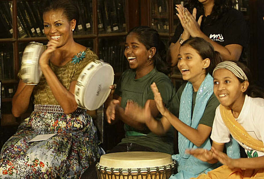 "U.S. first lady Michelle Obama, left, plays a ""Duff"" an Indian percussion instrument, with underprivileged children at the Mumbai University in Mumbai, India, Saturday, Nov. 6, 2010. U.S. President Barack Obama began a 10-day trip through Asia on Saturday. Photo: Rajanish Kakade, AP"