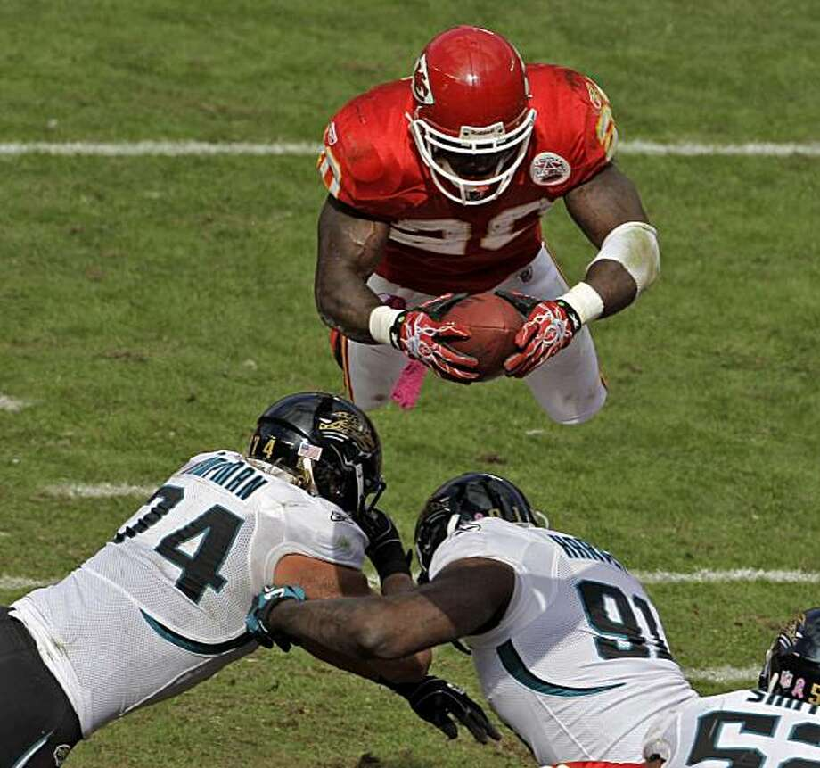Kansas City Chiefs running back Thomas Jones (20) dives over Jacksonville Jaguars defensive end Aaron Kampman, left, and defensive end Derrick Harvey (91) to score a touchdown during the second quarter of an NFL football game, Sunday, Oct. 24, 2010, in Kansas City, Mo. Photo: Charlie Riedel, AP
