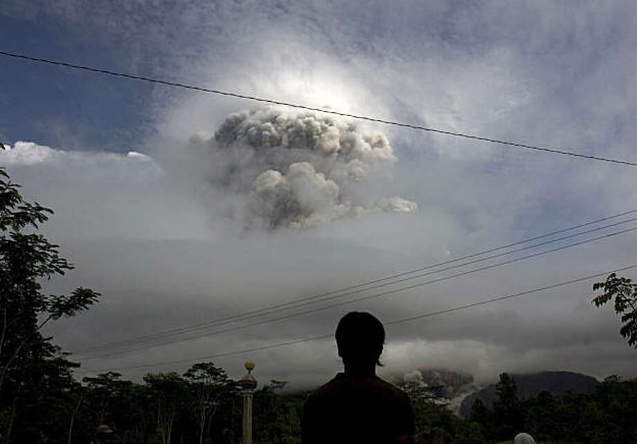 An Indonesian man watches as Mount Merapi erupts in Kepuharjo, Yogyakarta, Indonesia, Wednesday, Nov. 3, 2010. Indonesia's most dangerous volcano is once again sending searing gas clouds and burning rocks down its scorched flanks. Photo: Gembong Nusantara, AP