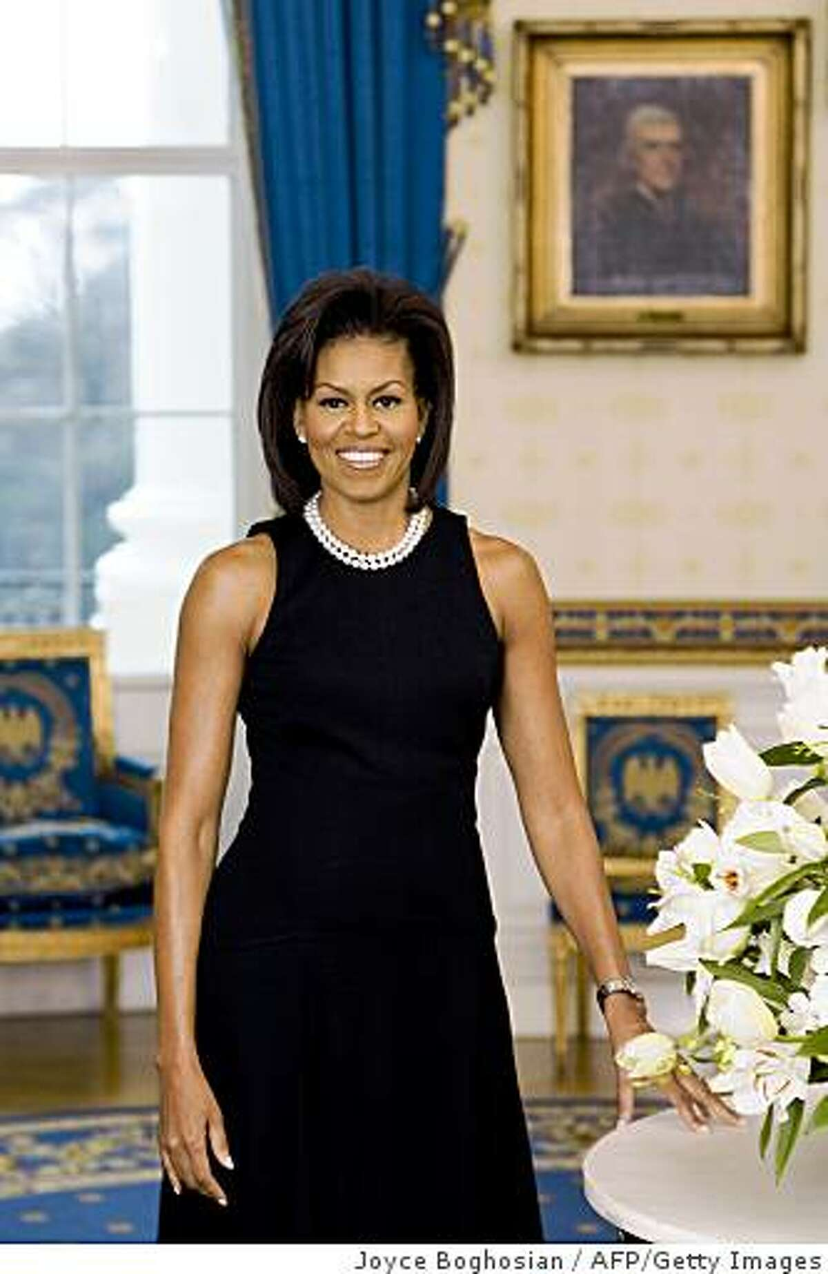 TO GO WITH AFP STORY BY VIRGINIE MONTET(FILES) Filed handout image released on Feberuary 27, 2009 by the White House in Washington, DC, shows First Lady Michelle Obama in her official portrait. The portrait shows Mrs. Obama standing in the Blue Room in a black sleeveless dress with a double strand of pearls. If one woman symbolizes International Women's Day for Americans, and black American women in particular, it's Michelle Obama, the successful career-woman and mother of two who six weeks ago became First Lady, March 6, 2009 AFP reported.AFP PHOTO/HO/THE WHITE HOUSE = RESTRICTED TO EDITORIAL USE = GETTY OUT = (Photo credit should read JOYCE BOGHOSIAN/AFP/Getty Images)