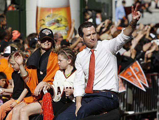 San Francisco Mayor Gavin Newsom, right, celebrates with his family as they ride in a car during a baseball World Series parade in downtown San Francisco, Wednesday, Nov. 3, 2010. Newsom is the California Lt. Governor-elect after winning in Tuesday's election. The Giants defeated the Texas Rangers in five games for their first championship since the team moved west from New York 52 years ago. Photo: Paul Sakuma, AP