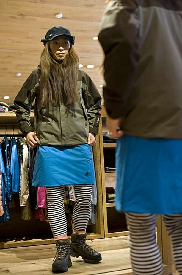 "Minako Yoshikoshi, a staff member of Goldwin Inc.'s North Face Harajuku store, tries on trekking wear popular with Japanese women in their 20s and 30s, in Tokyo, Japan, on Tuesday, Nov. 2, 2010. North Face, maker of the Gore-Tex waterproof jacket, and Alpine Tour Service Co. are targeting ""yama girls,"" or mountain girls, the nickname of the growing number of women who are taking to the hills of Japan wearing short pants or fleece skirts with leggings and designer trekking boots. Photographer: Robert Gilhooly/Bloomberg *** Local Caption *** Minako Yoshikoshi Photo: Robert Gilhooly, Bloomberg"