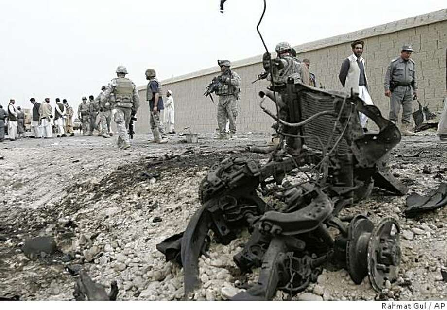 U.S. soldiers and Afghan police men inspect near the wrecker of a car used by a suicide bomber in Chaparhar district of eastern Nangarhar province, east of Kabul, Afghanistan, Saturday, March 21, 2009. A suicide bomber in a car blew himself up at a police checkpoint in Chaparhar district of eastern Nangarhar province where officers were searching cars, killing six people, including five civilians and one policeman, said police spokesman Gafor Khan. The blast also wounded four civilians and a policeman, he said. (AP Photo/Rahmat Gul) Photo: Rahmat Gul, AP