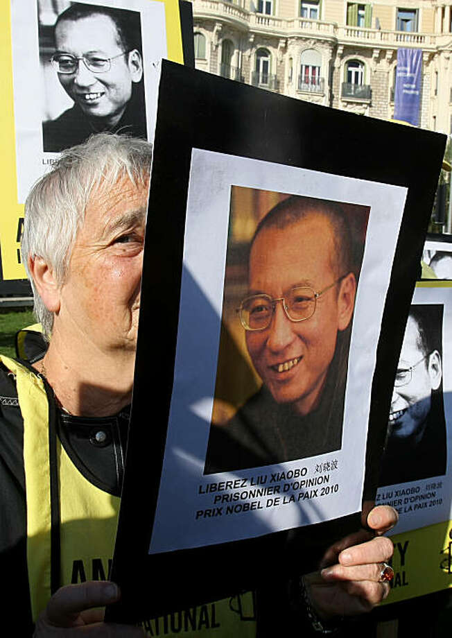 "Demonstrator holds a placard to protest the visit of Chinese President Hu Jintao in Nice, southeastern France, Friday Nov. 5, 2010. Placard read ""Release Liu Xiaobo, prisoner of opinion, 2010 Nobel prize of peace"". Photo: Lionel Cironneau, AP"