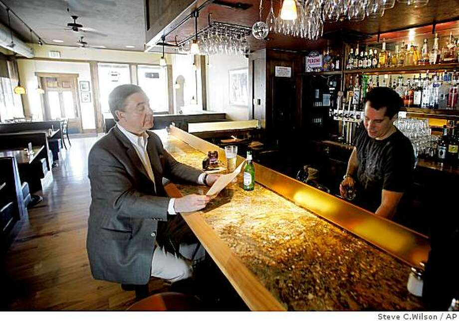 """Jeffrey Holtz, left, in town on business from St. Louis, looks over the lunch menu while bartender Mark Cannella serves him at Cannella's Restaurant on Wednesday, March 18, 2009, in Salt Lake City. The green divider known as a """"Zion Curtain"""" creating a visual barrier between the restaurant area and the area behind the bar where the drinks are prepared will no longer be needed after May 12 in existing restaurants in Utah, but new restaurants will be required prepare drinks out of customer's  sight under a bill approved by the Utah legislature March 12.  (AP Photo/Steve C. Wilson) Photo: Steve C.Wilson, AP"""