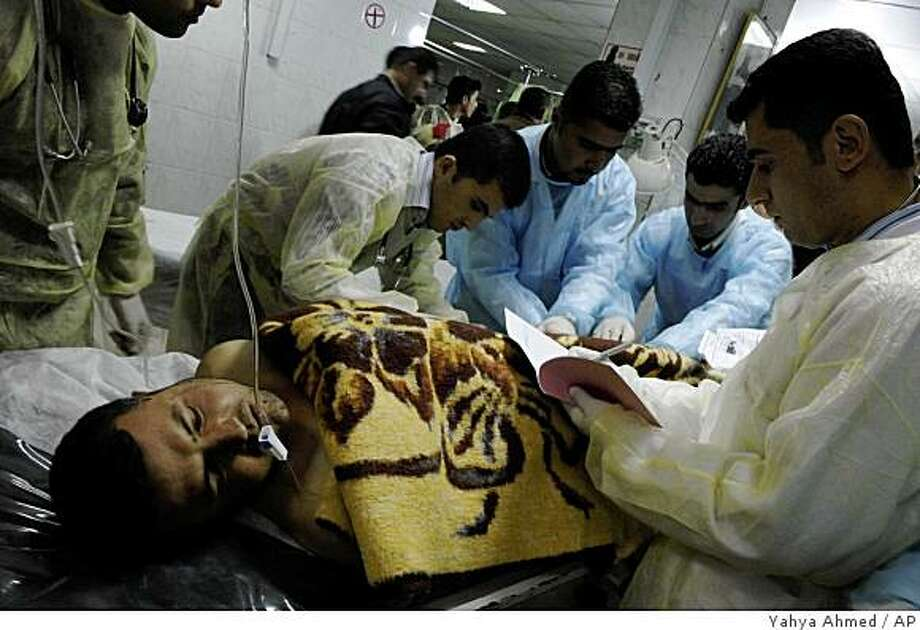 A man wounded in a suicide bombing in Jalulu, 125 kilometers (80 miles) northeast of Baghdad, Iraq, is helped by medics at a hospital in Sulaimaniyah, Iraq, Monday, March 23, 2009.  A suicide bomber struck a Kurdish funeral tent in Jalulu Monday, officials said, in the deadliest of a series of attacks that killed 24 people nationwide. (AP Photo/Yahya Ahmed) Photo: Yahya Ahmed, AP