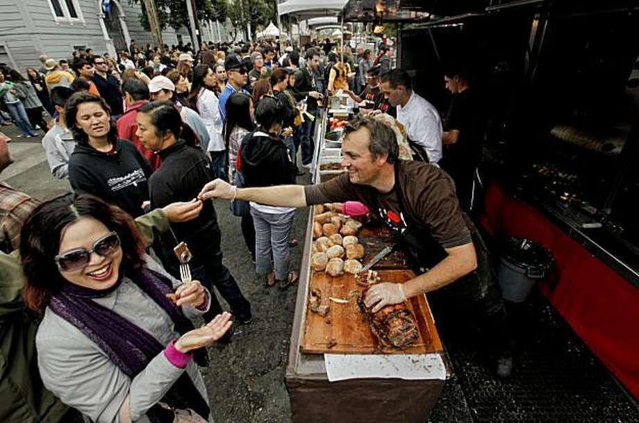 Thomas Odermatt passes out pork loin wrapped in pork belly at the San Francisco Street Festival. Photo: Michael Macor, The Chronicle