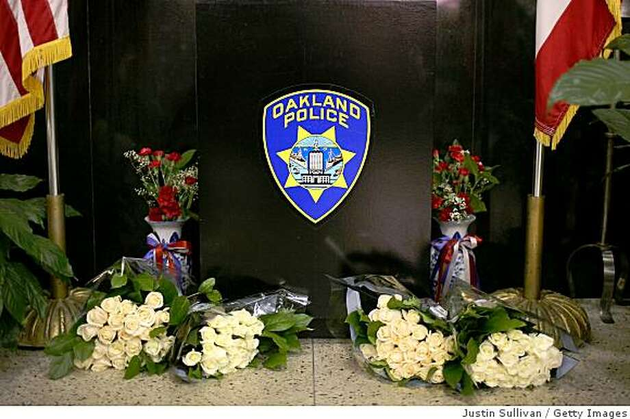 OAKLAND, CA - MARCH 21: Four bouquets of flowers are placed at a memorial inside the lobby of the Oakland Police headquarters March 21, 2009 in Oakland, California. Three Oakland police officers have died and another remains in critical condition after a traffic stop, followed by a separate shootout with the suspect. The suspect was also shot and killed by police. (Photo by Justin Sullivan/Getty Images) Photo: Justin Sullivan, Getty Images